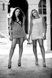 Stående av två sexiga flickor som står på gatainnehavhänder Arkivbilder