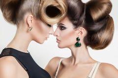 Stående av två sexiga kvinnor i studio med idérik hairst för volym Fotografering för Bildbyråer
