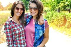 Stående av två skratta kvinnliga vänner som bär solglasögon som ser kameran royaltyfri fotografi