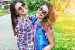 Stående av två skratta kvinnliga vänner som bär solglasögon som ser kameran arkivbilder