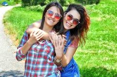 StÃ¥ende av tvÃ¥ skratta kvinnliga vänner som bär solglasögon som ser kameran fotografering för bildbyråer