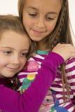 Stående av två unga flickor som kramar bärande pyjamas royaltyfria foton