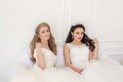 Stående av två unga kvinnor i bröllopsklänningar i vita Hall royaltyfri fotografi