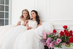 Stående av två unga kvinnor i bröllopsklänningar i vita Hall arkivfoton