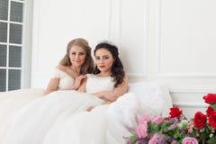 Stående av två unga kvinnor i bröllopsklänningar i vita Hall royaltyfria bilder