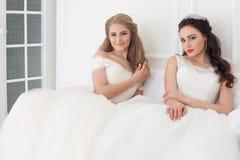 Stående av två unga kvinnor i bröllopsklänningar i vita Hall royaltyfria foton