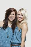 Stående av två unga kvinnor i liknande hoppdräkter som ler över grå bakgrund Arkivbild