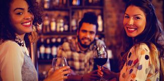 Stående av två unga kvinnor som har rött vin på räknaren royaltyfri bild