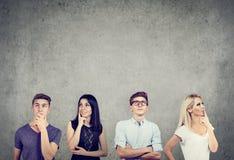 Stående av två unga män och två kvinnor som tänker hårt att se stå upp nära en betongvägg arkivfoto