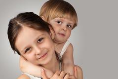 Stående av två unga systrar som omfamnar Royaltyfria Foton