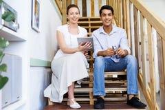 Stående av två ungdomarsom i regeringsställning sitter på trappan Arkivfoton