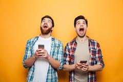 Stående av två upphetsade unga män som rymmer mobiltelefoner royaltyfria foton