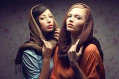 Stående av två ursnygga unga kvinnor (brunetten och rödhårigt) Arkivfoto