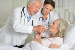 Stående av två yrkesmässiga doktorer som kontrollerar patienten royaltyfria foton