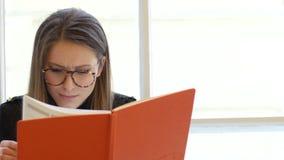 Stående av ung handstil för kvinnlig student i notepaden med exponeringsglas som sitter på fönsterbrädan stock video
