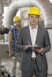 Stående av ung manlig chefhandstil på skrivplattan med den manuella arbetaren i bakgrund på bransch arkivfoto