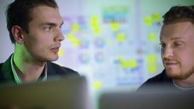 Stående av unga affärsmän som arbetar på övertid lager videofilmer