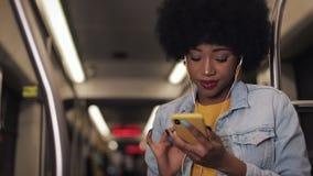 Stående av unga afrikansk amerikankvinnor i hörlurar som lyssnar till musik och offentligt bläddrar på mobiltelefonen lager videofilmer