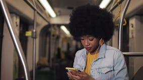 Stående av unga afrikansk amerikankvinnor i hörlurar som lyssnar till musik och offentligt bläddrar på mobiltelefonen stock video