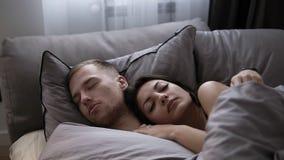 Stående av unga caucasian par som hemma sover i sängen på de gråa sängarken Frukost för en person lager videofilmer