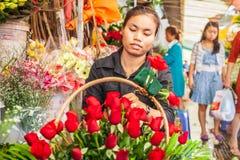 Stående av unga en khmerblomsterhandlarekvinnor som gör skönhetbuketten av röda rosor på vandringsledet Phsa Thmei marknad, Phnom royaltyfria foton