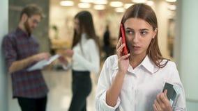 Stående av unga flickan med katalogen som talar vid mobiltelefonen i arbetsplats på bakgrunden av att prata folk långsamt stock video