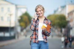 Stående av unga flickan mot den suddiga gatan som talar på telefonen arkivfoton