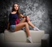 Stående av unga flickan på soffan Royaltyfria Foton