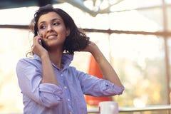 Stående av unga flickan som talar på telefonen, medan dricka kaffe arkivbild