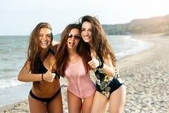 Stående av unga kvinnliga vänner som har gyckel på havskusten som ser att skratta för kamera Nätt brunbränt bära för kvinnor royaltyfria bilder