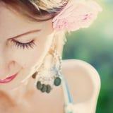 Stående av unga kvinnor med rosa färgrosen i hennes hår Arkivfoton