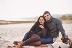 Stående av unga lyckliga par i en kall dag vid hösthavet Arkivfoto