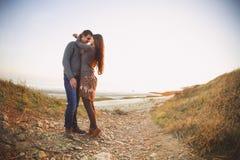 Stående av unga lyckliga par som skrattar i en kall dag vid havet Fotografering för Bildbyråer