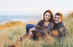 Stående av unga lyckliga par som skrattar i en kall dag vid havet Arkivbild