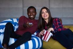 St?ende av unga par som sitter p? soffan som h?ller ?gonen p? en film med uttryck p? deras framsidor royaltyfria bilder