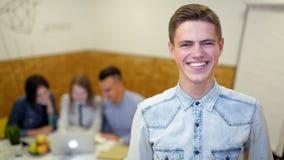 Stående av unga Team Leader i kontoret med hans Team Working på projekt arkivfilmer