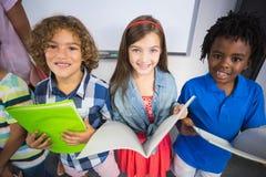 Stående av ungar som rymmer boken i klassrum royaltyfria foton