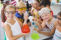 Stående av ungar som rymmer laboratoriumflaskan i laboratorium Arkivfoton