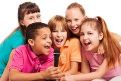 Stående av ungar som tillsammans sjunger Arkivbild