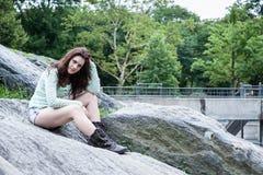 Stående av ungt brunettsammanträde på boudersna royaltyfri foto