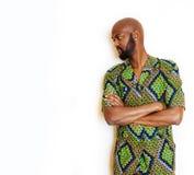 Stående av ungt stiligt afrikanskt bära för man som är ljust - grön nationell dräkt som ler att göra en gest, underhållningmateri arkivfoto