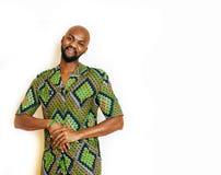 Stående av ungt stiligt afrikanskt bära för man som är ljust - grön nationell dräkt som ler att göra en gest, underhållningmateri royaltyfri foto