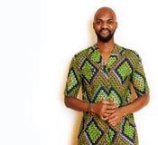 Stående av ungt stiligt afrikanskt bära för man som är ljust - grön nationell dräkt som ler att göra en gest, underhållningmateri royaltyfri bild