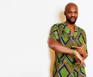 Stående av ungt stiligt afrikanskt bära för man som är ljust - grön nationell dräkt som ler att göra en gest, underhållningmateri royaltyfria foton
