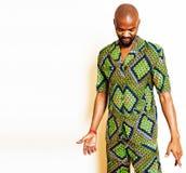 Stående av ungt stiligt afrikanskt bära för man som är ljust - grön nationell dräkt som ler att göra en gest, underhållningmateri fotografering för bildbyråer