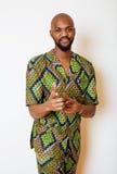 Stående av ungt stiligt afrikanskt bära för man som är ljust - grön nationell dräkt som ler att göra en gest fotografering för bildbyråer