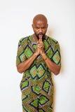 Stående av ungt stiligt afrikanskt bära för man som är ljust - grön nationell dräkt som ler att göra en gest royaltyfri foto