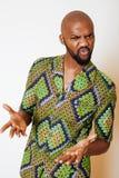 Stående av ungt stiligt afrikanskt bära för man som är ljust - grön nationell dräkt som ler att göra en gest arkivbilder
