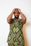 Stående av ungt stiligt afrikanskt bära för man som är ljust - grön nationell dräkt som ler att göra en gest arkivbild