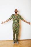 Stående av ungt stiligt afrikanskt bära för man som är ljust - grön nationell dräkt som ler att göra en gest royaltyfri bild